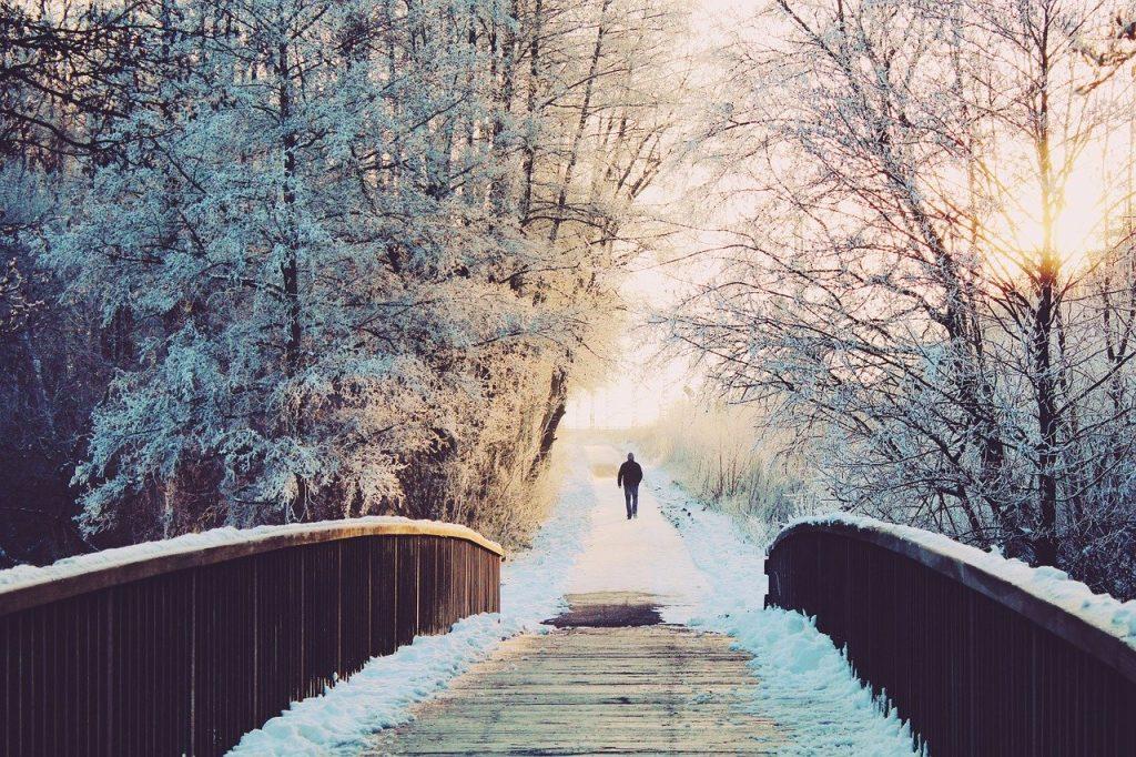luminen talvimaisema jossa yksinäinen kulkija sillalla