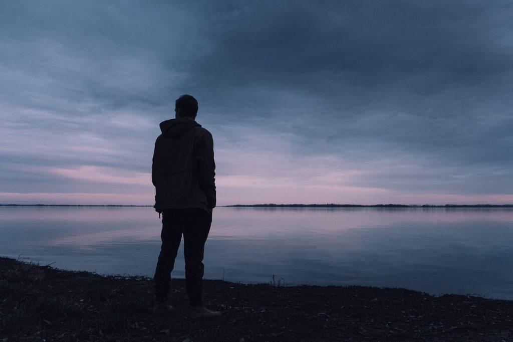 Kuva: mies seisoo järven rannalla